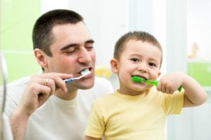 Father and son smiling and brushing their teeth