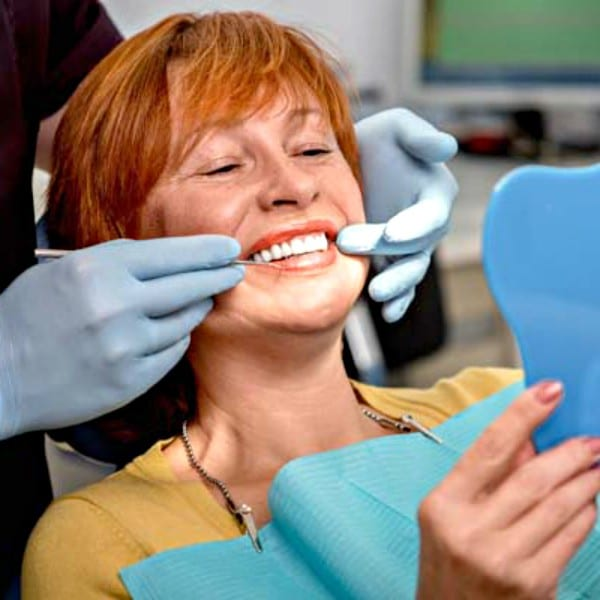 Woman with red hair examining her smile with her dentist