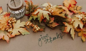 """A cluster of fall leaves next to a candle on brown paper with the words """"give thanks"""" to celebrate Thanksgiving"""