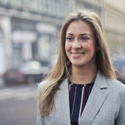 Smiling blonde-haired woman wearing a business blazer and blouse while standing by a pedestrian crosswalk in a city